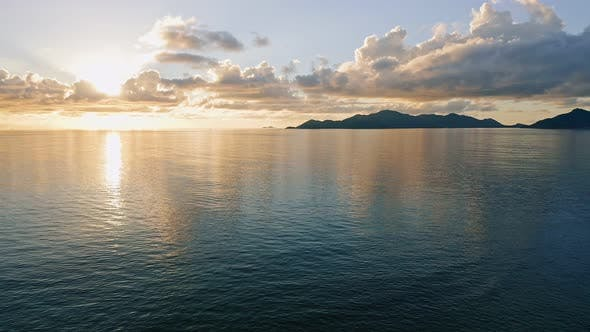 Aerial  Footage of Sunset and Open Calm Ocean with Tropical Island Silhouette on Horizon