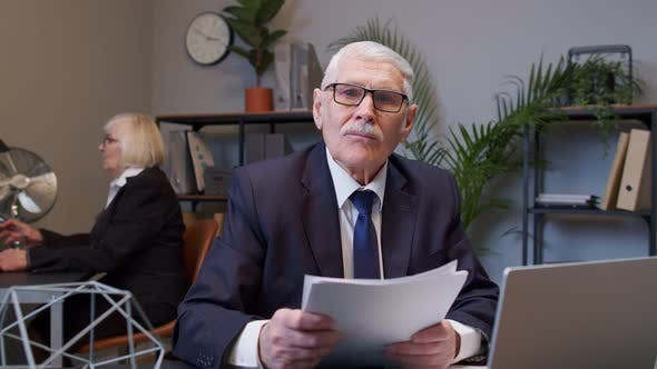 Senior Business Company Manager Sitting at Office Desk Reading Resume Successful Job Interview