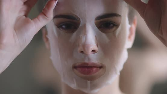 Portrait of a Beautiful Woman, Paper Sheet Masks on Face, Female Slowly Removes a Beauty Mask From