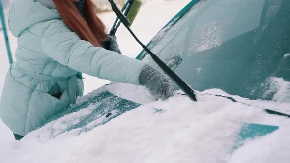 Thumbnail for Woman Removes Snow From Windshield of Car