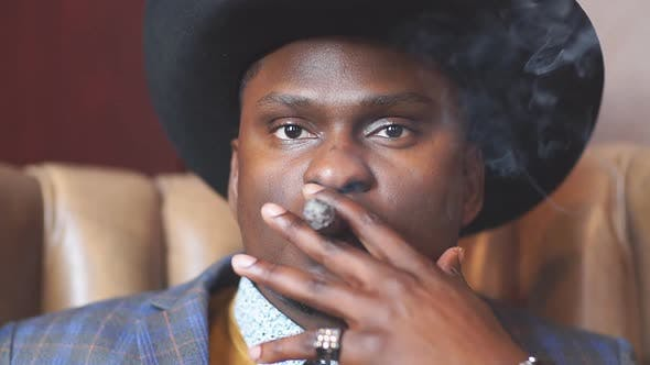 Gangster look. Handsome man with hat and cigar. Slow motion