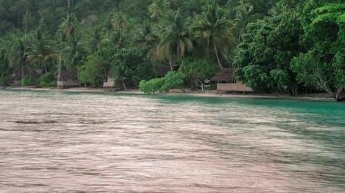 Tropical Rain Over the Bamboo Homestay Huts on the Beach, Gam Island, Raja Ampat, West Papua