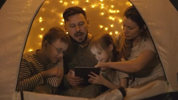 Thumbnail for Family Members Using Tablet in Tent