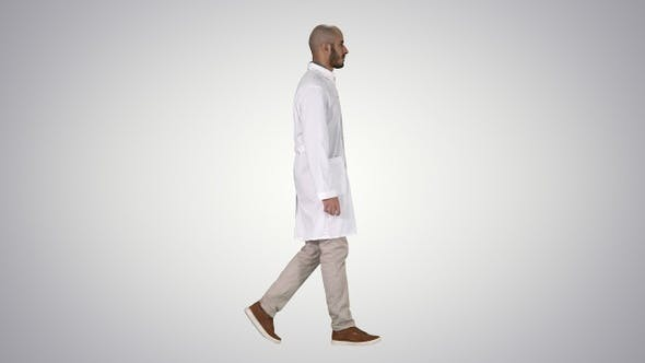 Thumbnail for Arabian doctor in white robe walking on gradient background.