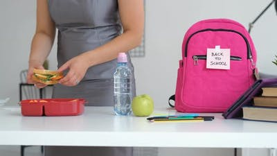 Woman Puts School Lunch in Backpack of Daughter