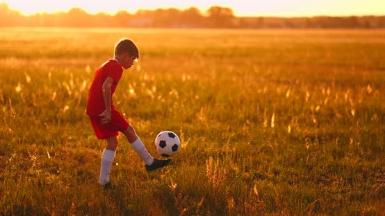 Thumbnail for Boy Football Player at Sunset Juggling the Ball in the Field