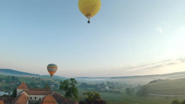 Colorful Hot Air Balloons Fly Over the Medieval Castle and Lake in the Morning Fog. Maneuverable