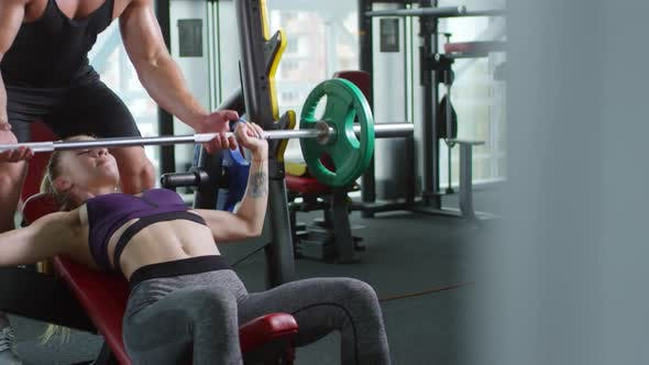 Cover Image for Woman Doing Bench Press with Trainer