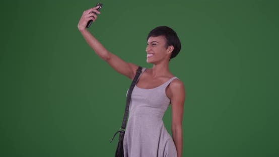 Thumbnail for Woman blowing kiss and taking a selfie picture with smartphone on green screen
