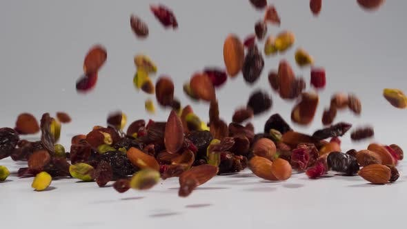 Healthy trail mix falling onto a white surface in slow motion