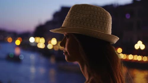 Silhouette of tourist woman in fedora looking out at Grand Canal