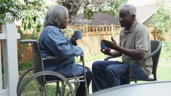 Thumbnail for Disabled elderly black woman drinking coffee with husband