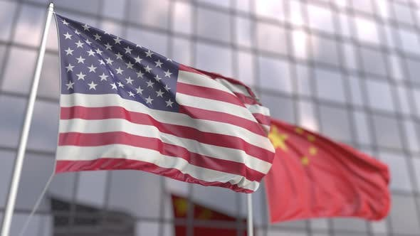 Waving Flags of the USA and China in Front of a Skyscraper