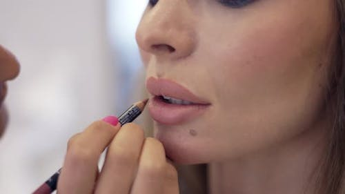 The Makeup Artist Contours the Model's Lips with a Nude Beige Pencil Closeup