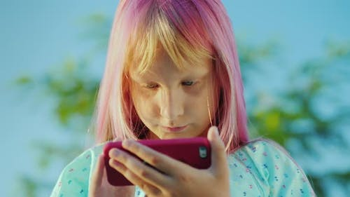 Portrait of Cool Girl with Pink Hair Is Talking Through a Smart Watch