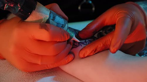 Close Up Tattoo Artist Draws a Picture on the Hand of a Young Woman, the Process of Creating a