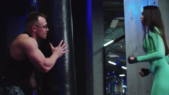Woman Having a Boxing Training with a Coach  Hitting the Punching Bag