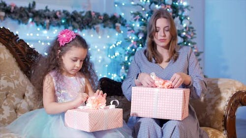 Young Happy Mother With Her Little Sweet Daughter Open a Gifts, Look Inward and Rejoice in the