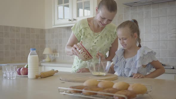 Thumbnail for Pretty Young Mother and Little Cute Daughter Cook in the Kitchen Together