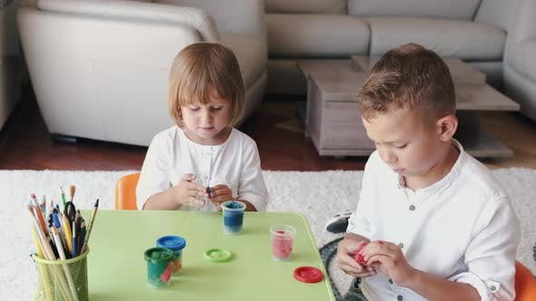 Thumbnail for Portrait of Two Kids Holding Plasticine and Making Figurines