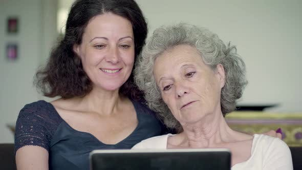 Thumbnail for Daughter and Mother Holding Tablet, Googling and Swiping Photos