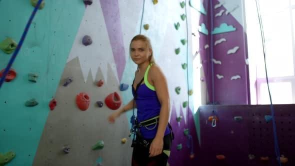 Thumbnail for Junge kaukasische Frau posiert neben Kletterwand im Fitness-Studio