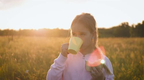 Cute Little Girl in the Field Eating a Bread and Drinking Milk at Sunset. Healthy Eating Concept.