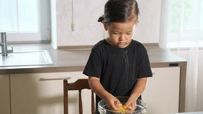 Funny Toddler Squeezes Egg Which Splashes on Black Shirt