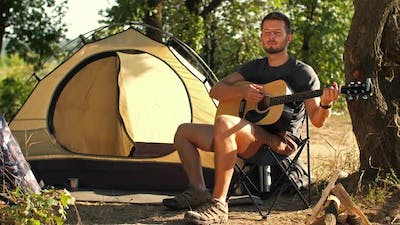 Backpacker with Guitar at Forest