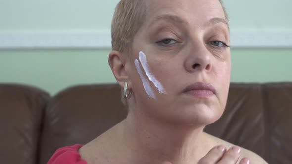 Mature Woman Applying Facial Cream on the Face While Looking at Camera. Consept Skin Care