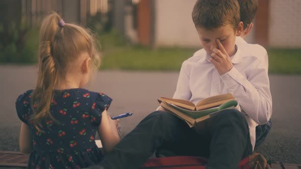 Little Girl with Pencil Talks To Boy Reading Book on Street