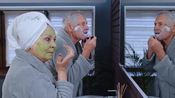 Senior Grandmother Applying Facial Mask and Grandfather Shaving with Manual Razor Blade at Bathroom