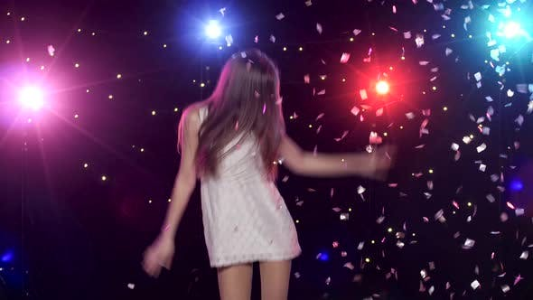 Thumbnail for Carefree Girl Dancing and Throws Glitter Confetti Against Disco Lights
