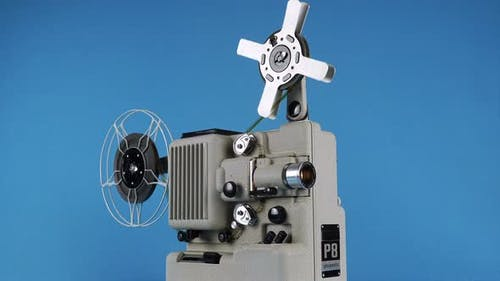 Rotating Vintage Movie Projector On A Blue Background.