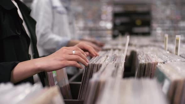 Thumbnail for Male and Female Customers Browsing through Music Records in Shop
