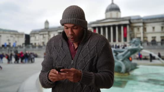 Thumbnail for Modern African-American male sending text message on phone at Trafalgar Square