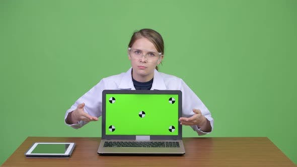 Thumbnail for Young Beautiful Woman Doctor with Protective Glasses Presenting Something with Laptop