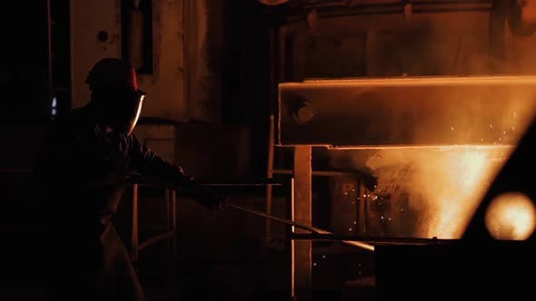 Thumbnail for Steel Worker in Protective Clothing raking Furnace in an Industrial Foundry.