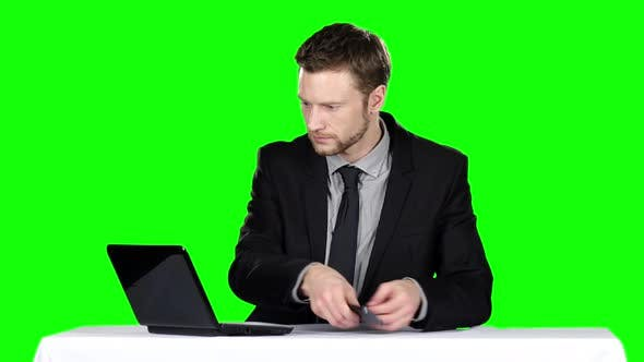 Thumbnail for Businessman Sitting at a Desk and Using Notebook and Calling on the Phone. Green Screen