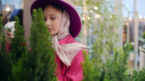 Cute Girl in Pink Hat Spraying Plants in Indoor Garden Orangery