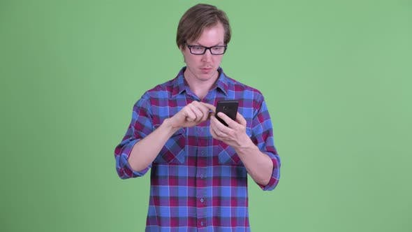 Thumbnail for Young Handsome Hipster Man Using Phone and Looking Shocked