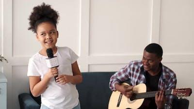 African Father Playing Guitar Daughter Singing