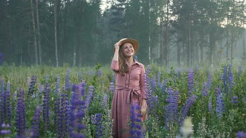 Blonde Woman Throws Away Hat Among Purple Lupin Flowers