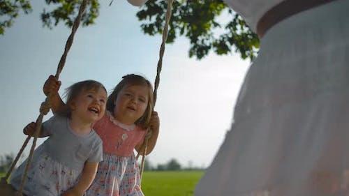 Zwei kleine Mädchen schwingen auf einer Schaukel