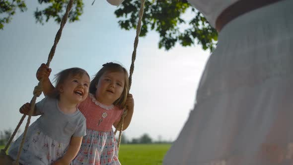 Thumbnail for Two Little Girls Swinging on a Swing