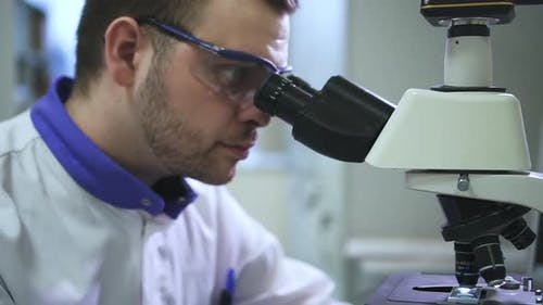Man Professional is Working with Microscope and Pc at Table in Pharmaceutical Laboratory Spbd