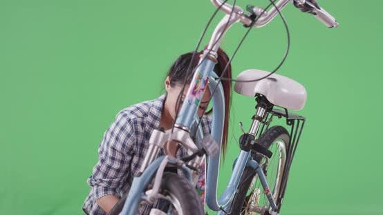 Thumbnail for Asian woman giving her bicycle a quick tuneup on green screen