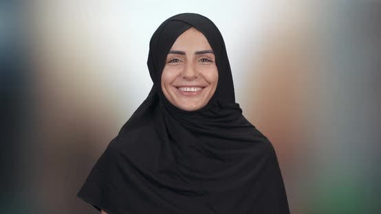 Portrait of a Beautiful Muslim Woman, a Happy Woman in a Hijab Looks at the Camera and Smiles