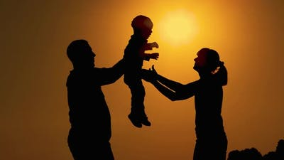 Silhouettes at sunset.  Dad hands the little baby over to mom. mom rotates with the baby