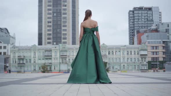 Back View of Gorgeous Girl in a Stunning Evening Green Dress Walking Fascinatingly on Empty City